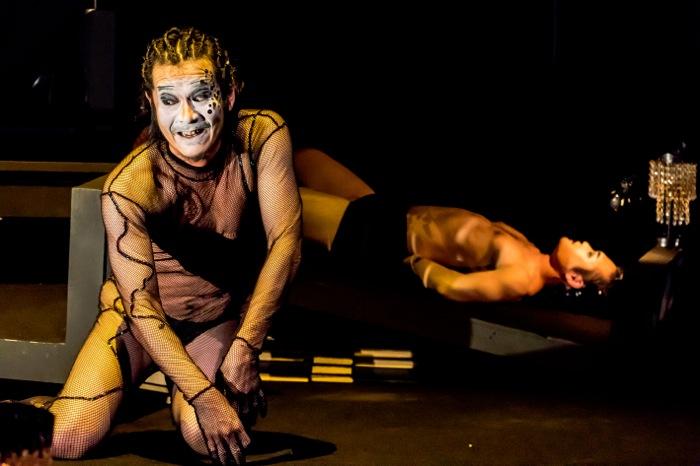 劇団山の手事情社『テンペスト』 【写真】キャリバン(岩淵吉能)の背後でベッドに縛り付けられた男が呻く 撮影=平松俊之