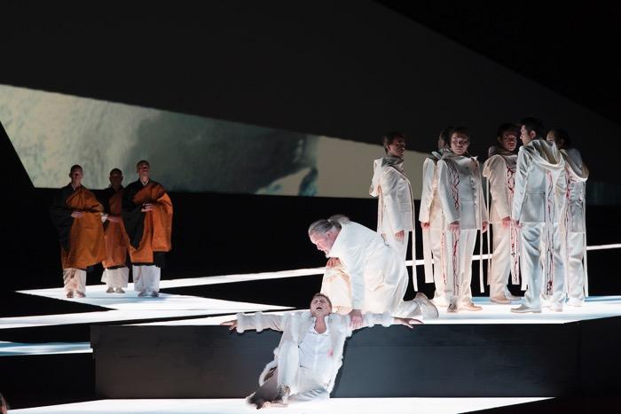 第一幕、手前は傷ついたアムフォルタス王(エギルス・シリンス)、右に聖杯騎士団、左に和風の仏僧。撮影:寺司正彦/提供:新国立劇場